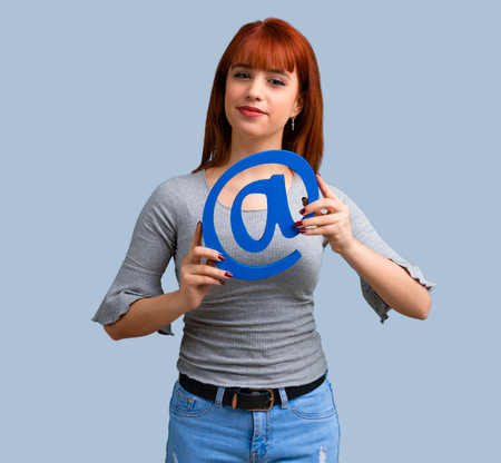 Young redhead girl holding icon of at dot com on blue background