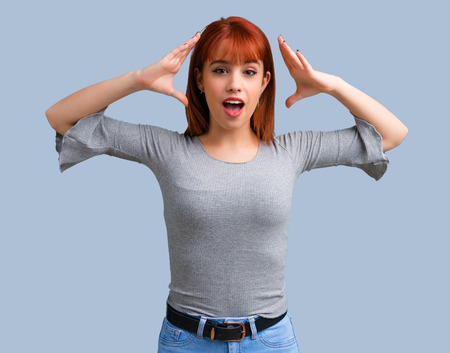 Young redhead girl with surprise and shocked facial expression on blue background