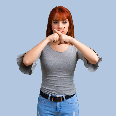 Young redhead girl showing a sign of closing mouth and silence gesture on blue background