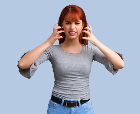 Young redhead girl annoyed and angry in furious gesture on blue background Stockfoto