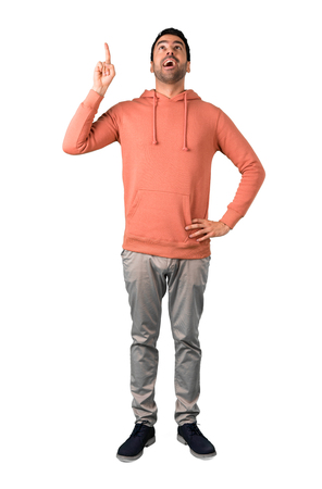 Full body of Man in a pink sweatshirt standing and thinking an idea pointing the finger up on isolated white background