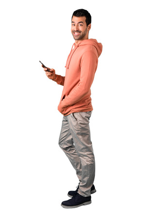 Full body of Man in a pink sweatshirt looking at the camera and smiling while using the mobile on isolated white background