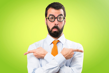 Funny man with glasses pointing to the laterals having doubts on colorful background