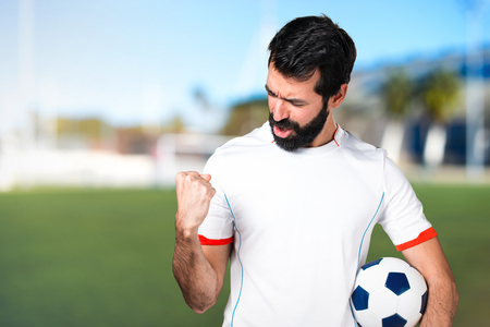 Lucky football player holding a soccer ball on a football pitch