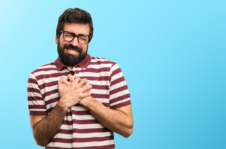 Man with glasses with heart pain on colorful background Stock Photo