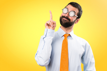 Funny man with glasses pointing up on colorful background