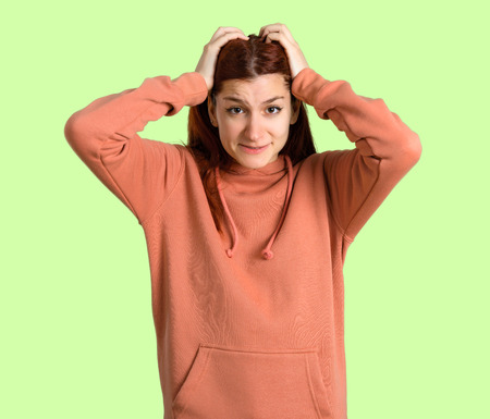 Young redhead girl with pink sweatshirt takes hands on head because has migraine on green background