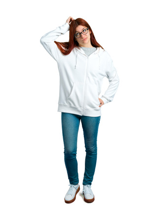 Young redhead girl in an urban white sweatshirt with glasses having doubts and with confuse face expression while scratching head on isolated white background