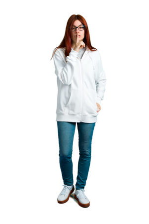 Young redhead girl in an urban white sweatshirt with glasses showing a sign of closing mouth and silence gesture putting finger in mouth on isolated white background