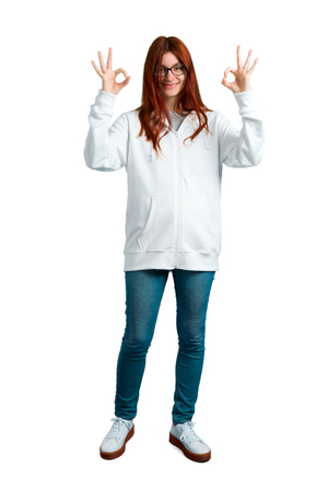 Young redhead girl in an urban white sweatshirt with glasses showing an ok sign with fingers. Face of happiness and satisfaction on isolated white background Stock Photo