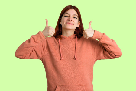 Young redhead girl with pink sweatshirt giving a thumbs up gesture and smiling because has had success on green background
