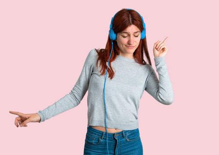 Young redhead girl listening to music with headphones and dancing on isolated pink background Foto de archivo - 104069455