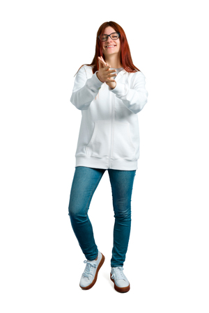 Young redhead girl in an urban white sweatshirt with glasses smiling and applauding on isolated white background