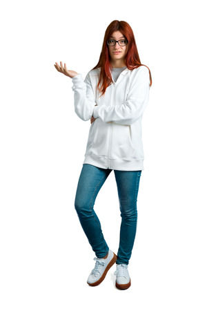 Young redhead girl in an urban white sweatshirt with glasses unhappy and frustrated with something. Negative facial expression on isolated white background