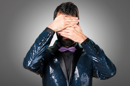 Handsome man with sequin jacket covering his face on grey background Stock Photo