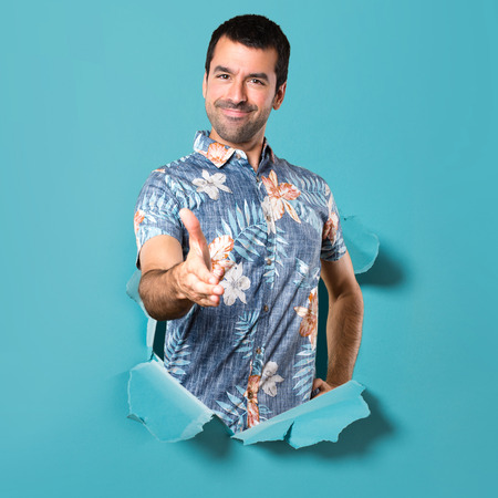 Handsome man with flower shirt making a deal through a blue paper hole Stockfoto