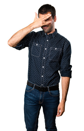 Brunette man covering his eyes on isolated white background Stock Photo