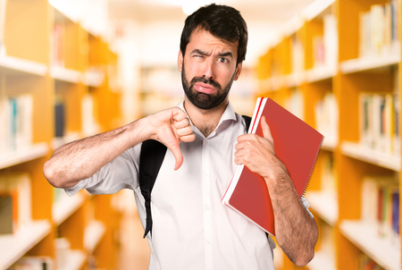 Student man making bad signal on defocused library Stock Photo