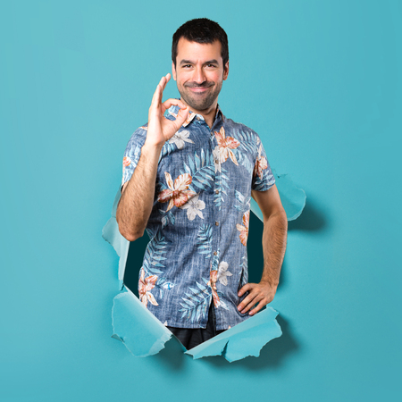 Handsome man with flower shirt making OK sign through a blue paper hole