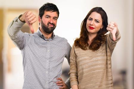 Young couple making bad signal on unfocused background Stock Photo