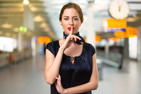 Pretty stewardess making silence gesture inside the airport