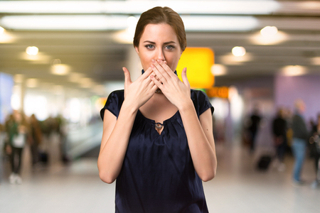 Pretty stewardess covering her mouth inside the airport