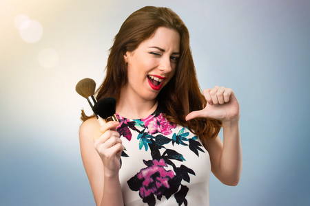 Beautiful young girl with makeup brush proud of herself on unfocused background Imagens