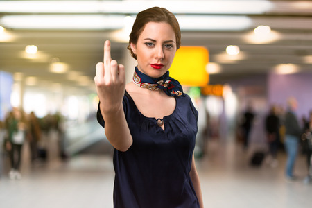 Pretty stewardess making horn gesture inside the airport