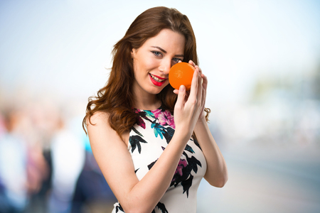 Happy beautiful young girl holding oranges on unfocused background