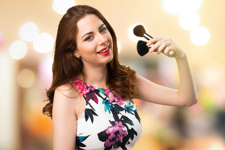 Happy beautiful young girl with makeup brush on unfocused background Imagens