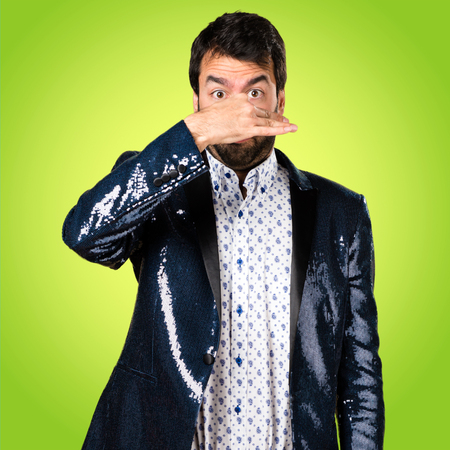 Man with jacket making smelling bad gesture on colorful background Stock Photo