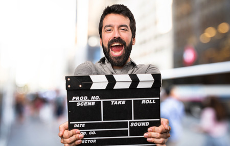 Handsome man with beard holding a clapperboard at outdoor