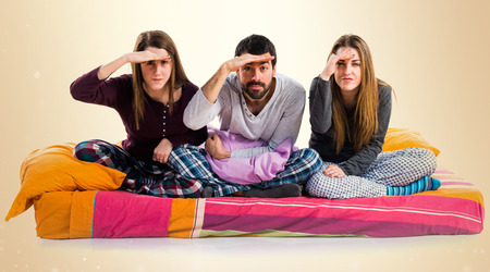 Three friends on a bed showing something