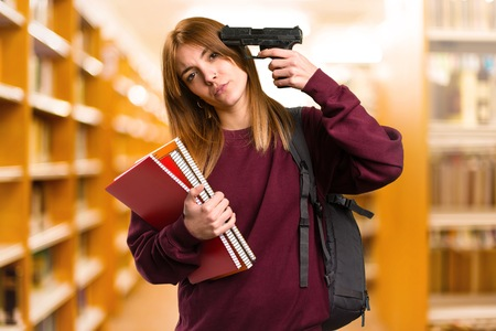 Student woman cometing suicide on unfocused background Stock Photo