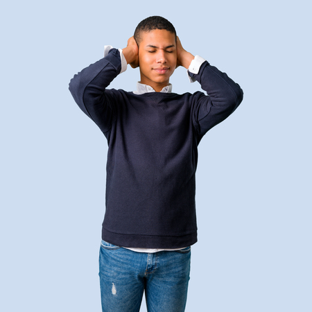 Young african american man covering both ears with hands on isolated blue background Stock Photo