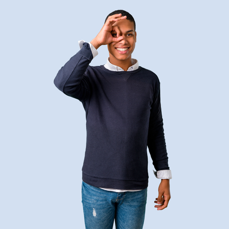 Young african american man makes funny and crazy face emotion on isolated blue background