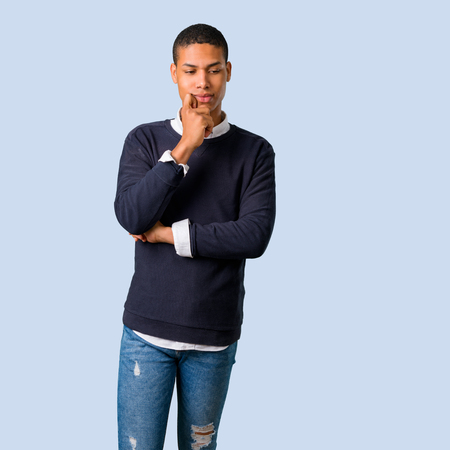 Young african american man standing and looking down on isolated blue background