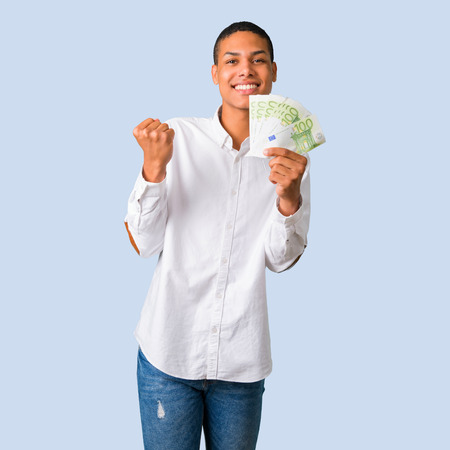Young african american man with white shirt happy because has won a lot of money on isolated blue background Stock Photo