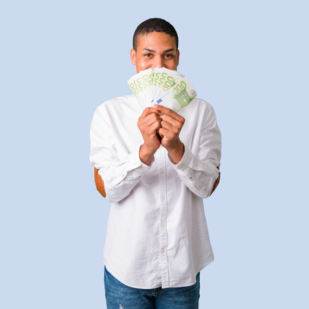 Young african american man with white shirt taking a lot of money on isolated blue background Stock Photo