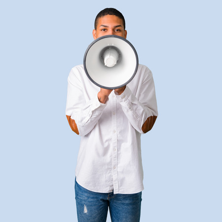 Young african american man with white shirt shouting through a megaphone to announce something on isolated blue background