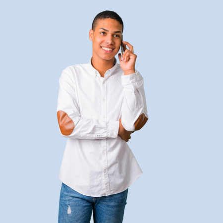 Young african american man with white shirt keeping a conversation with the mobile phone with someone on isolated blue background Stock Photo