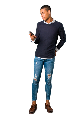 Young african american man sending a message or email with the mobile on isolated white background. Ideal for use in architectural designs