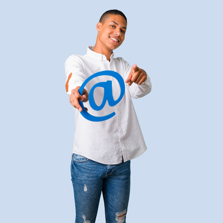 Young african american man with white shirt holding icon of at dot com and pointing to the front on isolated blue background Stock Photo
