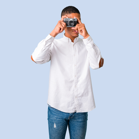 Young african american man with white shirt holding a camera and photographing something on isolated blue background