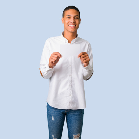 Young african american man with white shirt holding an empty white placard for insert a concept on isolated blue background