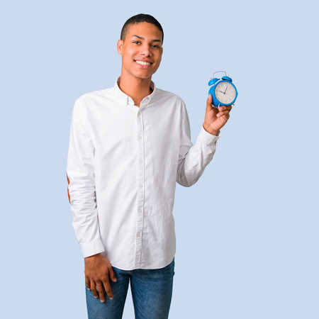 Young african american man with white shirt holding vintage alarm clock on isolated blue background Stock Photo