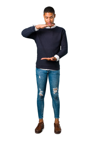 Young african american man holding copy space imaginary on the palm to insert an ad on isolated white background