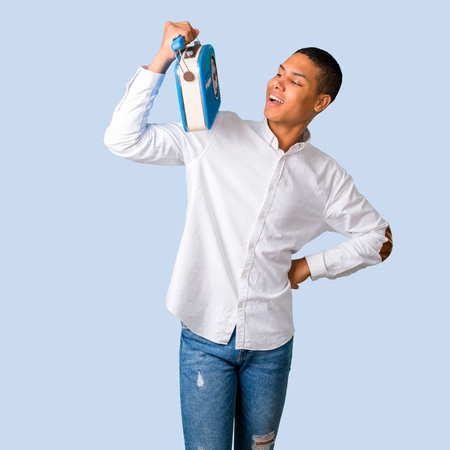 Young african american man with white shirt holding a blue vintage radio while singing on isolated blue background