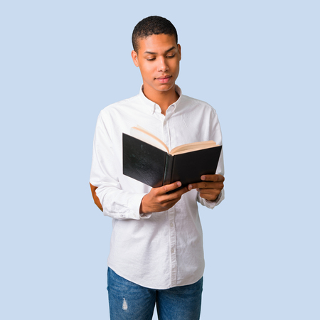 Young african american man with white shirt holding a book and enjoying reading on isolated blue background Stock Photo