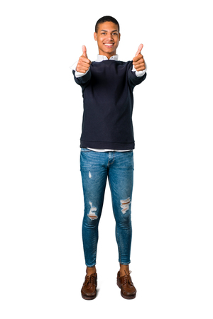 Young african american man giving a thumbs up gesture with both hands and smiling. Cheerful expression on isolated white background